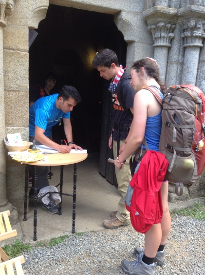 Katie and Tyler getting a stamp for the compostela